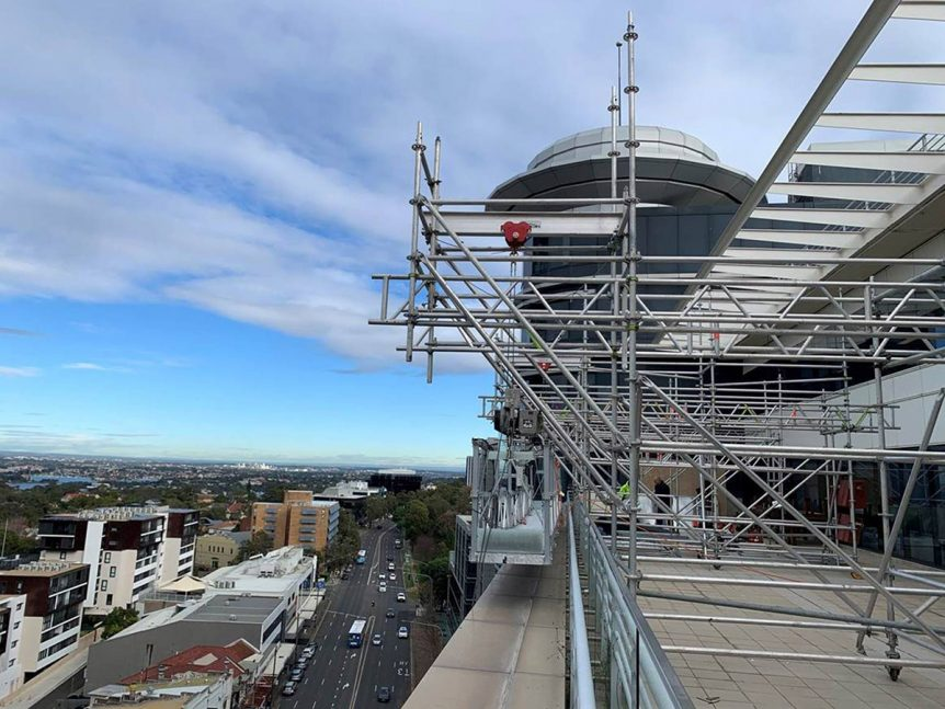 CJ Duncan using sky hooks on an elevated swinging platform for Combustible Cladding replacement project in St Leonoards